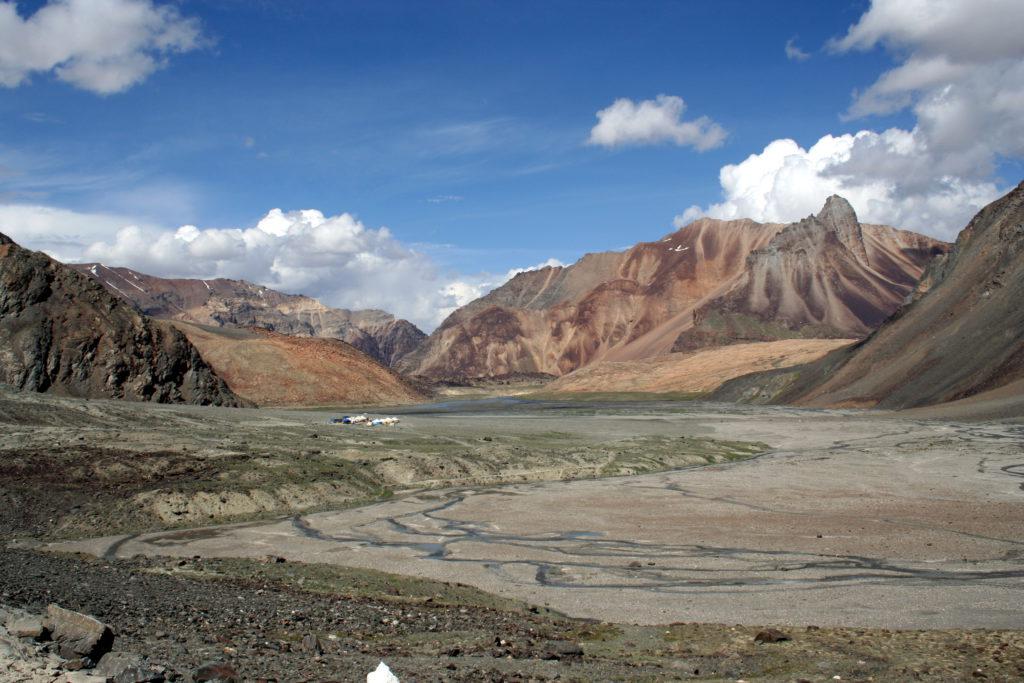 Nachdem die Pässe zwischen Himachal Pradesh und Jammu-Kaschmir überwunden sind, finden wir uns am Ladakhischen Hochplateau wieder. Im Osten schließt es an Tibet, im Nordwesten an das pakistanische Kaschmir und Baltistan, im Süden an Spiti und Lahaul an. Die Zeltstädte, wie hier am Bild, bieten dem Reisenden Rast, Momos (gefüllte Teigtaschen) und Chai (süßen Gewürztee mit Milch).