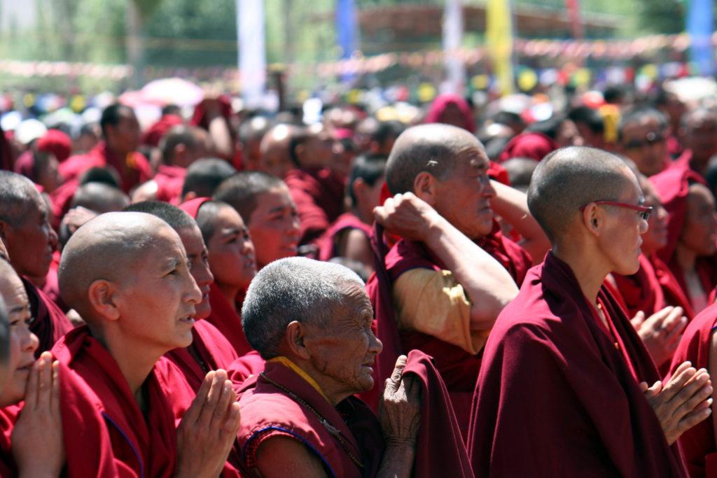 """Nonnen und Mönche bei der Vorlesung des Dalai Lama in Choglamsar. Man beachte den Ausdruck von Hingabe an den Moment in den Gesichtern. Nicht umsonst ist der tibetische Beiname Seiner Heiligkeit """"Kundün"""", was soviel wie """"Gegenwart"""" bedeutet."""