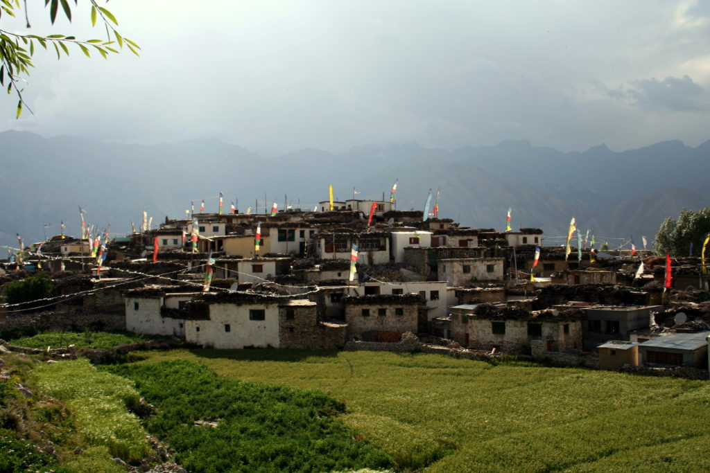 """Das Dörfchen Nako trennen nur etwa 30 Kilometer Luftlinie von der Grenze zu Tibet. Was hier so ungewohnt grün leuchtet, ist Hochland-Gerste. Die Gebetsfahnen haben in den letzten Jahren Gesellschaft durch Satellitenschüsseln bekommen, die für einen tadellosen Empfang von """"Desperate Housewives"""" sorgen-"""